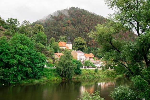 Igreja antiga pelo rio na paisagem montanhosa em um dia nublado
