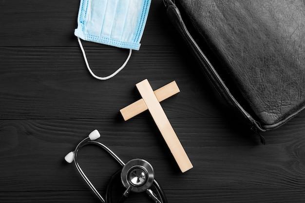 Igreja com cruz de madeira, máscara facial, sobre fundo de madeira. conceito cristão.