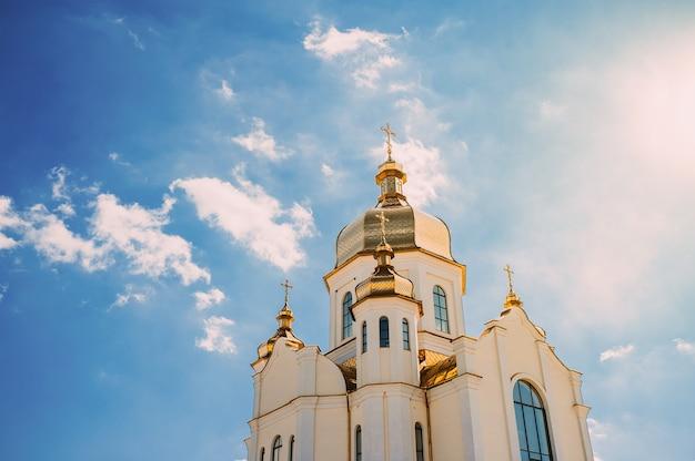 Igreja com cúpulas douradas contra um céu azul com nuvens