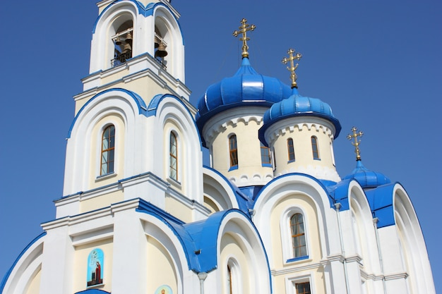 Igreja cristã com cúpulas azuis escuras de cor branca contra o céu azul escuro