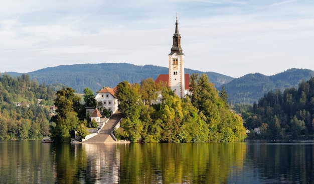 Igreja da assunção de maria na ilha do lago bled, eslovénia, com reflexos na água