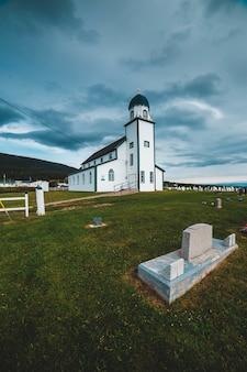 Igreja de madeira branca e preta sob nuvens cinzentas durante o dia