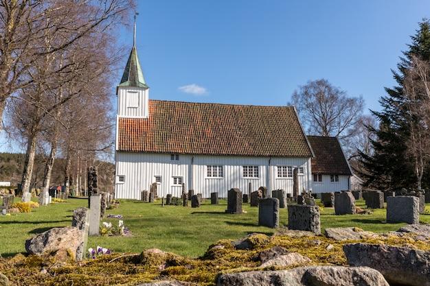Igreja de madeira branca em sogne, uma igreja paroquial em sogne, vest-agder na noruega. céu azul, grama verde.
