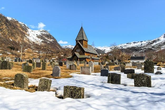 Igreja de madeira roldal (roldal stavkyrkje) com primeiro plano de cemitério de neve