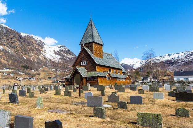 Igreja de madeira roldal (roldal stavkyrkje) com primeiro plano de cemitério