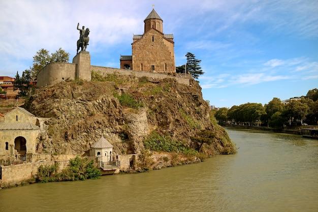 Igreja de metekhi com a estátua do rei vakhtang gorgasali na margem do rio mtkvari, tbilisi, geórgia
