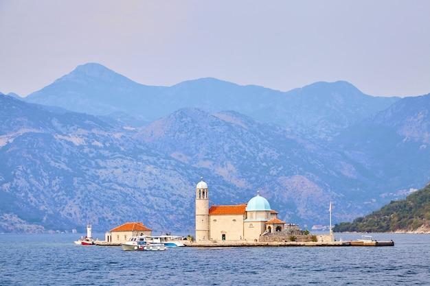 Igreja de nossa senhora das rochas na ilha na baía de boka kotor, montanhas, mar adriático, montenegro