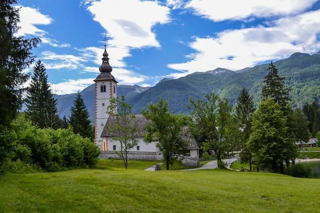 Igreja de pedra velha na margem de um lago de montanha. cordilheira verde e céu azul com nuvens brancas.