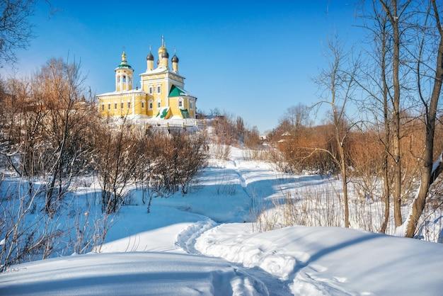 Igreja de são nicolau naberezhny e pegadas na neve em murom em um dia ensolarado de inverno com neve