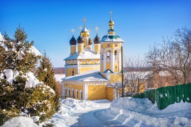 Igreja de são nicolau naberezhny e uma árvore conífera verde em murom em um dia ensolarado de inverno com neve