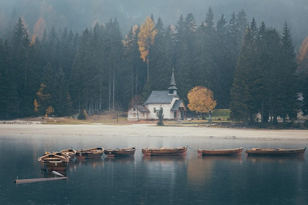 Igreja e barcos de madeira na imagem temperamental de lago di braies, tirada durante a chuva na temporada de outono, dolomitas, itália