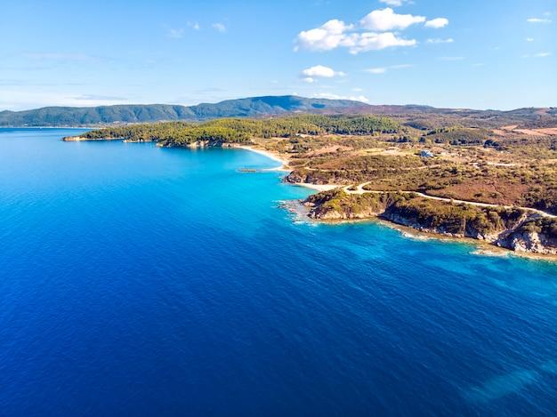 Igreja e mar com praia e montanhas em nea roda, halkidiki, grécia