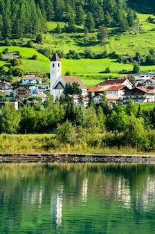 Igreja em graun im vinschgau ou curon venosta, uma cidade no lago reschen no tirol do sul, alpes italianos