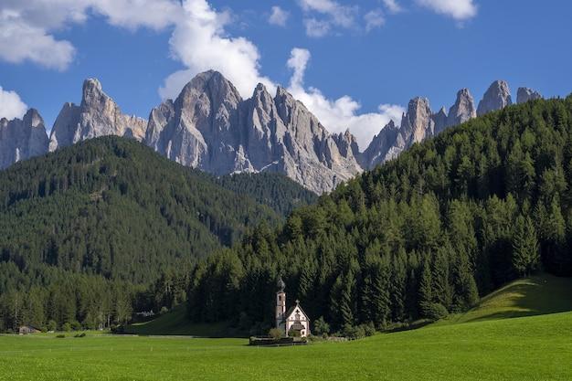 Igreja em uma paisagem verde cercada por montanhas rochosas no vale de funes, são itália