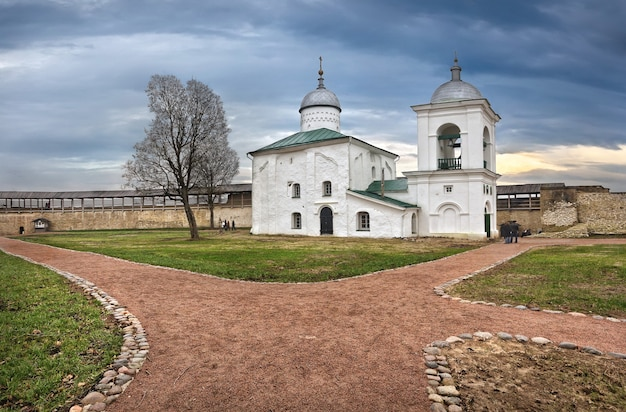 Igreja nikolskaya em izboursk (pskov) e a antiga muralha da fortaleza com torres em um dia nublado de outono