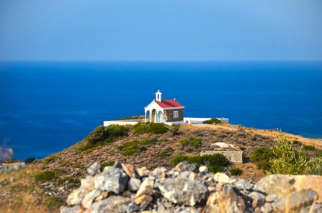 Igreja no topo de uma colina com vista para o mar azul