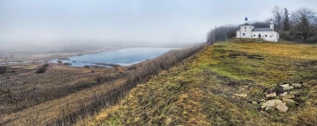 Igreja no vale izboursko-malskaya (pskov) e distância com neblina em um dia nublado de outono