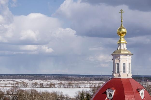Igreja ortodoxa cristã russa com cúpulas e uma cruz contra o céu.