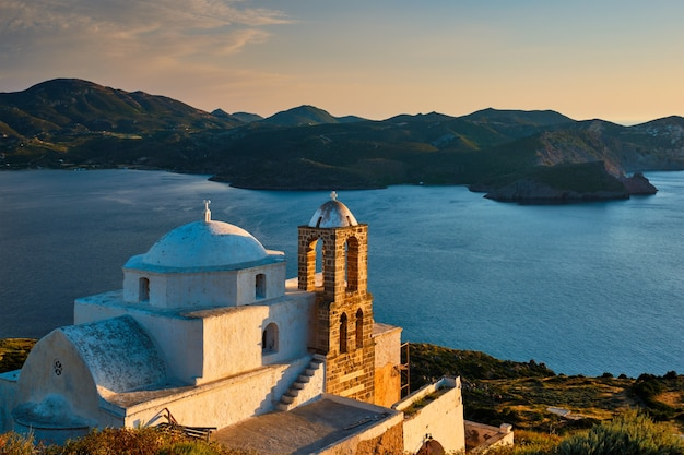 Igreja ortodoxa grega na aldeia de plaka, na ilha de milos, ao pôr do sol na grécia