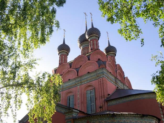 Igreja russa em torno de folhas verdes de vidoeiro no verão. a igreja da epifania