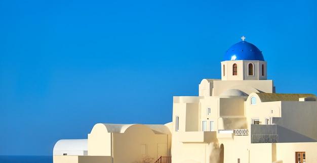 Igreja tradicional com cúpula azul na vila de oia, santorini, grécia
