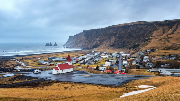 Igreja vermelha bonita e vila de vik, islândia.