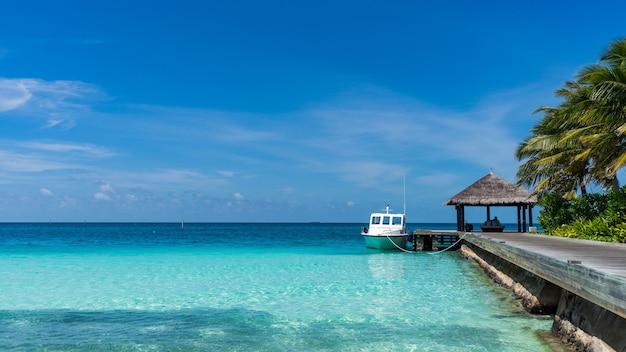 Ilha de luxo nas maldivas, cais de madeira no mar azul tropical. céu azul, dia de sol no resort das maldivas.