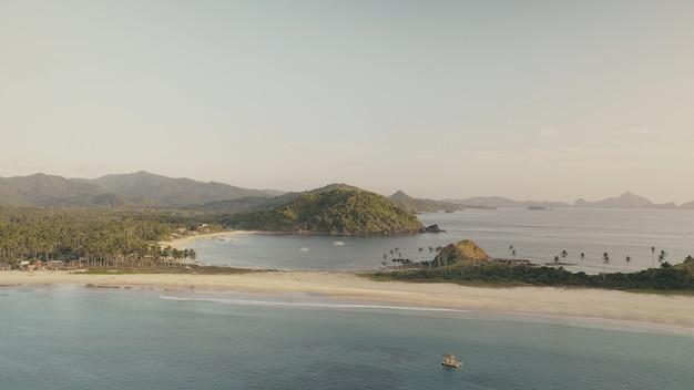 Ilha de montanhas verdes na antena da baía do oceano. tropical paisagem marinha de ninguém. água do mar serena na areia