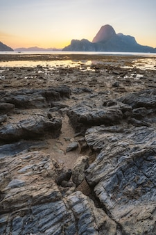 Ilha de palawan, filipinas. el nido lugar paradisíaco com a bela ilha de cadlao ao pôr do sol com costa rochosa na maré baixa.