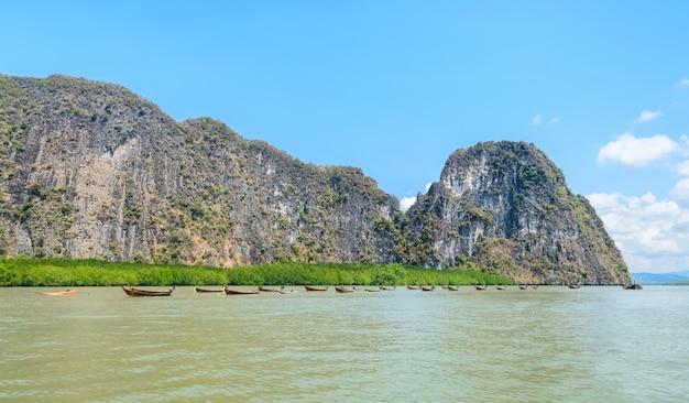 Ilha de pedra calcária com floresta de mangue e barcos de madeira de cauda longa no parque nacional da baía de phang nga, tailândia
