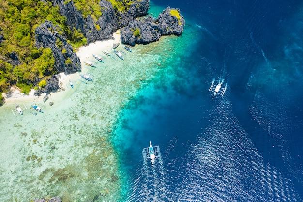 Ilha de shimizu, el nido, palawan, filipinas. vista aérea do drone de uma pequena ilha tropical com praia, recife de coral e falésias calcárias afiadas.