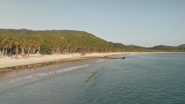 Ilha do paraíso tropical de el nido, filipinas, ásia. praia de areia na orla marítima com palmeiras