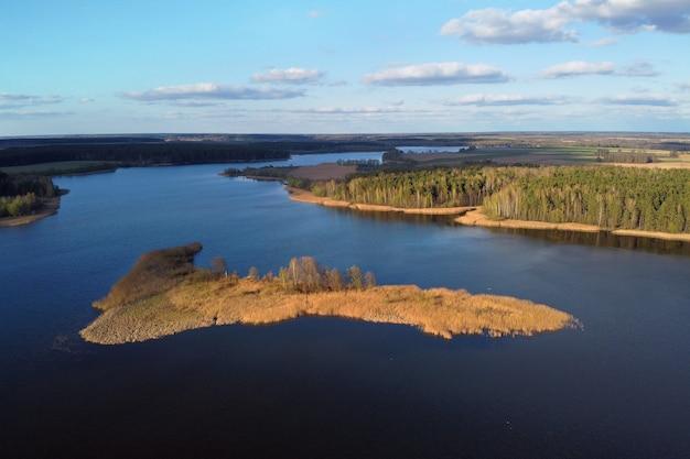 Ilha do rio e vista aérea da floresta. reservatório de armazenamento, lago. foto aérea de paisagem de primavera com céu azul e nuvens brancas, terreno plano