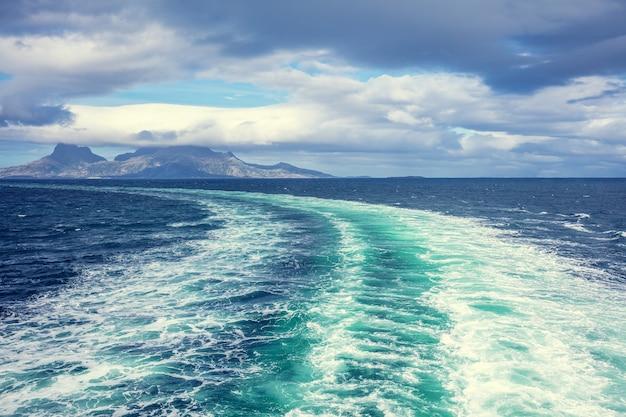Ilha no horizonte. pedras no mar. bela paisagem rochosa do mar com céu nublado dramático. trilha de água espumando atrás de uma balsa. vista do navio. natureza da noruega