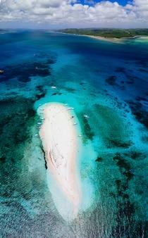 Ilha nua vista do céu. homem que relaxa tomando banho de sol na praia. tiro tomado com o zangão acima da cena bonita. conceito sobre viagens, natureza e paisagens marinhas