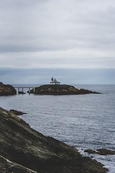 Ilha rochosa, cercada pelo mar sob um céu nublado
