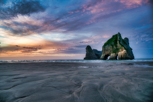 Ilhas archway, formações rochosas dramáticas sob céus de cores vibrantes em wharariki beach nelson