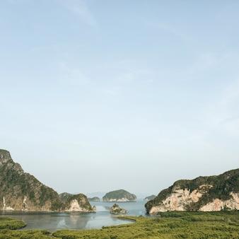 Ilhas exóticas e tropicais com rochas, mar azul e céu claro no parque nacional ao phang-nga
