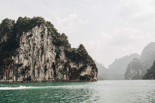 Ilhas exóticas e tropicais verde-escuras com rochas e lago verde no lago cheow lan, khao phang, distrito de ban ta khun
