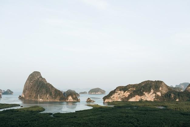 Ilhas exóticas e tropicais verde-escuras com rochas, mar azul e céu claro no parque nacional ao phang-nga