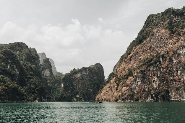 Ilhas exóticas e tropicais verde-escuras e marrons com rochas e lago verde no lago cheow lan, khao phang, distrito de ban ta khun
