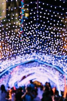 Ilumina o bokeh com os povos do borrão no fundo. festival de natal