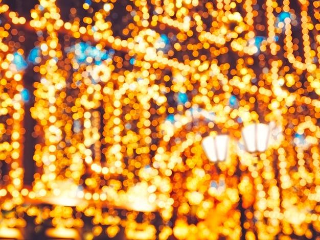 Iluminação brilhante da rua do natal na fachada do edifício. a cidade é decorada para o feriado christmastide. luzes do ano novo que decoram o bokeh cintilante.