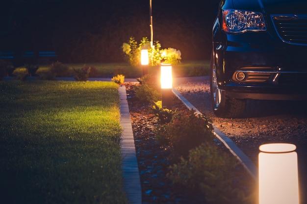 Iluminação da entrada de automóveis da casa. iluminação elegante do jardim da frente.
