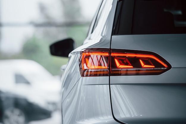 Iluminação de cor vermelha. vista de partículas de um carro branco luxuoso moderno estacionado dentro de casa durante o dia