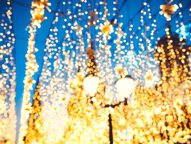 Iluminação de rua de natal brilhante na fachada dos edifícios. a cidade é decorada para o feriado christmastide. luzes de ano novo decorando bokeh cintilante