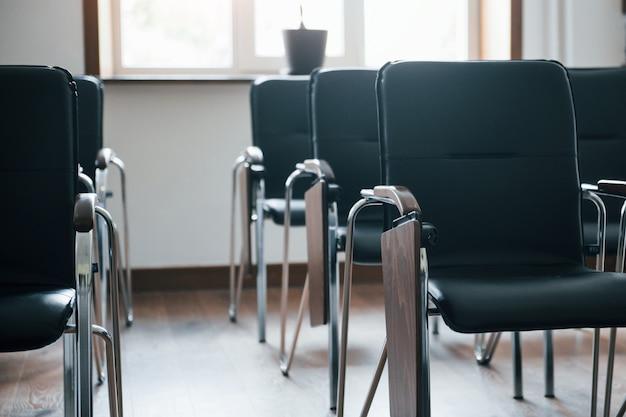 Iluminação natural. sala de aula de negócios durante o dia com muitas cadeiras pretas. pronto para alunos