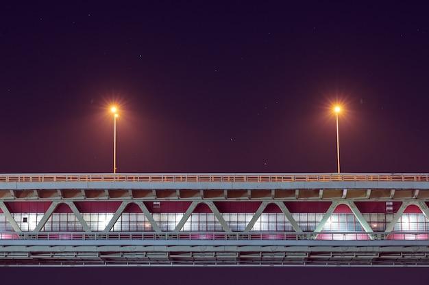 Iluminação noturna da ponte de trânsito rápido. luz minimalista, copie o espaço. dois postes com raio amarelo, fundo do céu crepúsculo azul roxo.