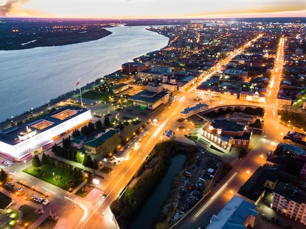 Iluminação noturna de tomsk. paisagem urbana vista aérea do rio tom. sibéria, rússia.