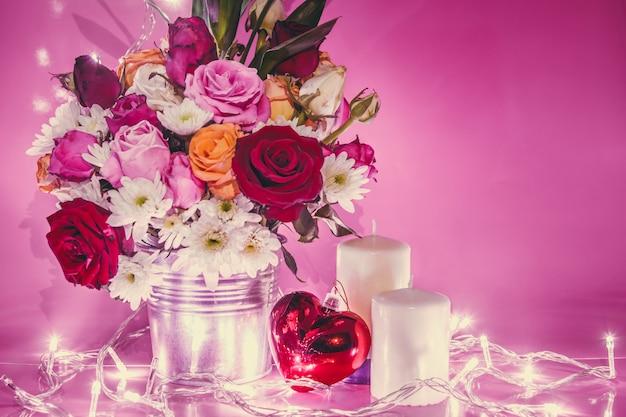 Iluminação vaso de buquê rosas, coração vermelho e vela branca